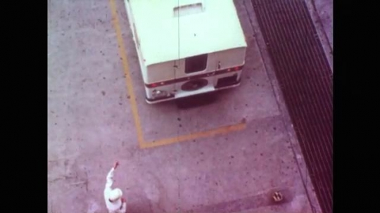 Man Waves  Van into Parking Spot on Concrete. Man Opens Van Door and Astronauts Step Out. .