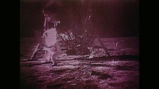 Astronaut Stood by Space Craft. Astronaut Walks Towards Astronaut on Surface of Moon. Astronaut Puts Something into the Ground