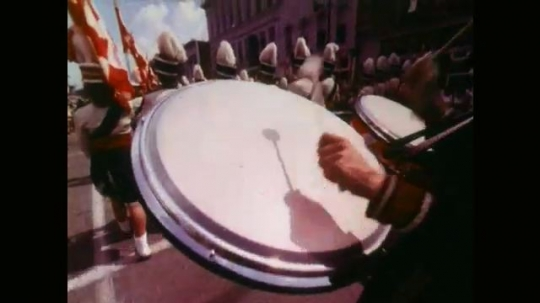 Man in Marching Band Bangs on Drums. Girls Marching in Street Parade and Waving Pompoms. Brass Band Playing as they March.