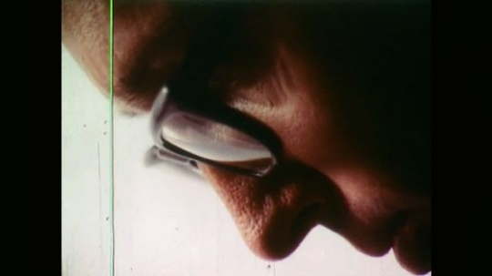Side View of Man Wearing Glasses. View of Petri Dish and Man Uses Tweezers to Pick up Tiny Fragments. Tiny Fragment Being Dropped into a Ceramic Bowl.