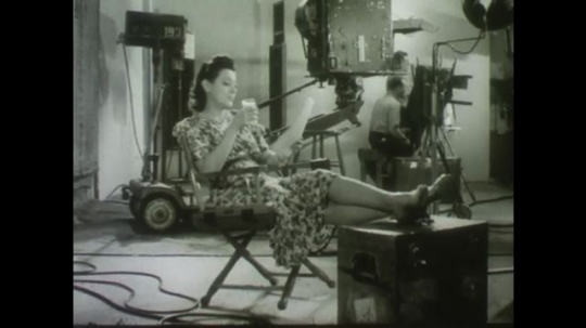 United States, 1940s: Lady putting her feet up and drinking glass of milk on film set. Crystal ball. Man next to shadow of cow with horns. Black and white cows in a field.