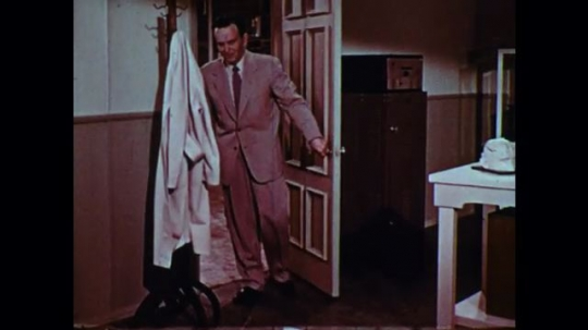 UNITED STATES 1950s: Man enters office, talks into camera, puts on lab coat, walks to desk, zoom in on man at desk.