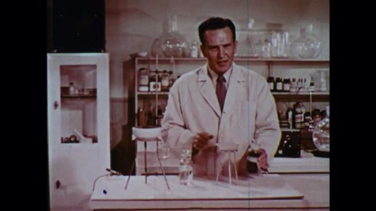 UNITED STATES 1950s: Man in lab pours liquids into bowl, walks away, bowl begins to smoke.