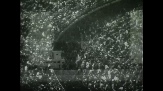BERLIN 1936: Large crowd in a stadium. Crowd makes 'Heil Hitler' hand sign. Italian team marches on track while making 'Heil Hitler' sign.