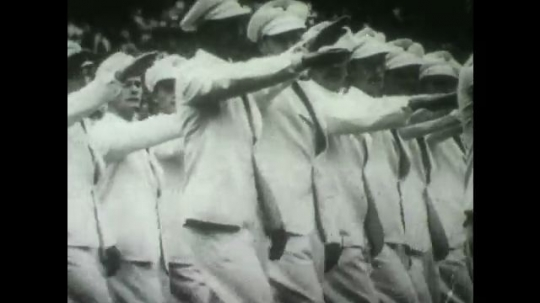 BERLIN 1936: Athletes march while saluting Hitler at Olympic opening ceremony. Person carries Olympic torch towards center of arena.