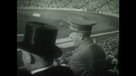 BERLIN 1936: Hitler cheers and athlete salutes him. Officials raise a flag with Swastika. Scoreboard showing country Olympic rankings. Top 3 winners in a category stand on podium saluting.