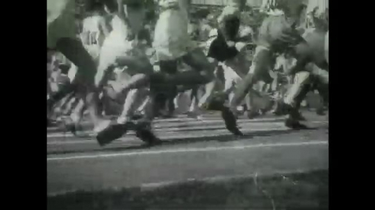 BERLIN 1936: Athletes compete in a running marathon. One stops to drink water quickly.