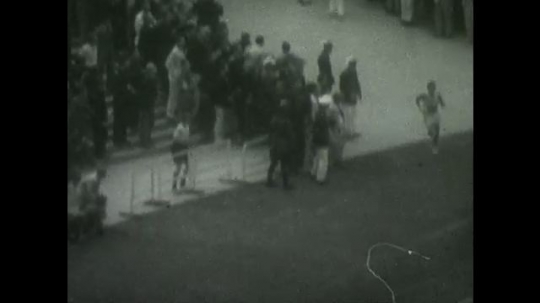 BERLIN 1936: One runner enters the field and begins running on the track.