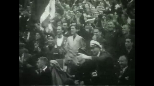 BERLIN 1936: Spectators in a stadium cheer wildly. Female competitor smiles and waves at them. Scoreboard shows