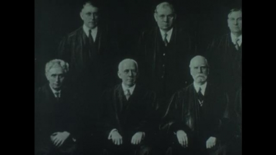 UNITED STATES 1940s: Pan of photo of supreme court justices / Judge sits at bench, animation of books over image.