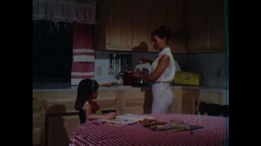 UNITED STATES 1960s: Woman in kitchen with girl, woman sits / Girl talking / Girl talks to woman at table / Close up of woman talking.