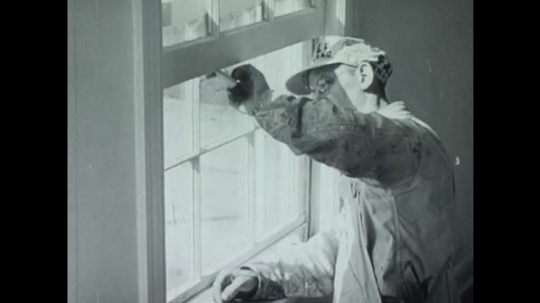 UNITED STATES 1940s: Man painting window frame / Hands clean with turpentine.