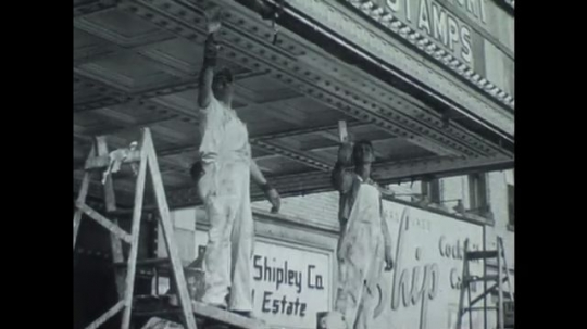 UNITED STATES 1940s: Men painting theater marquee / Low angle view, man painting marquee.