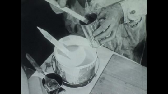 UNITED STATES 1940s: Hands mix pigment into paint / Man holds paint stirrer next to painted board.