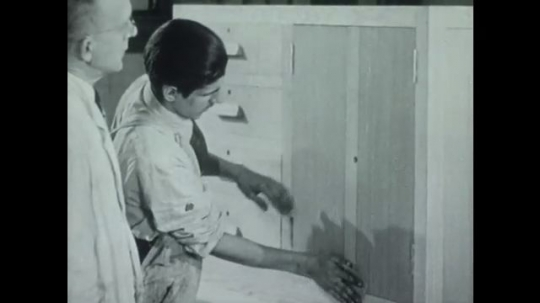 UNITED STATES 1940s: Man wipes stain from cabinet doors, instructor watches / Instructor watches man paint / View of marble pattern.
