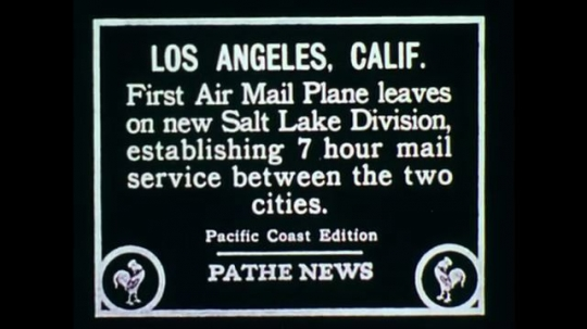UNITED STATES: 1970s: Pathe News information on first air mail plane. Vintage plane on runway. Car drives past crowd. People load US mail onto plane.