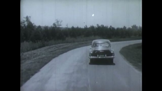 UNITED STATES: 1950s: View from behind as car drives along road and develops puncture.