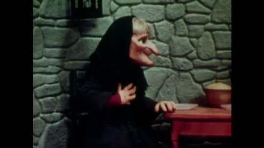 UNITED STATES: 1950s: Rapunzel and witch puppets sit down at a table together. Man walks along a track with his stick.