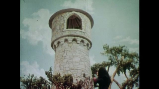 UNITED STATES: 1950s: Rapunzel throws down her hair for witch. Young man sees Rapunzel and her long hair. Young man falls in love with Rapunzel.