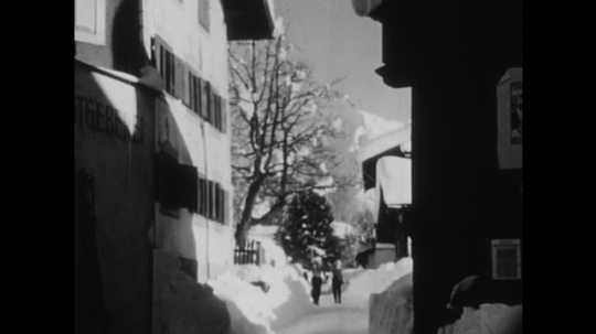 SWITZERLAND, 1950s: Man and woman walk through snow with ski gear past two men with cow.