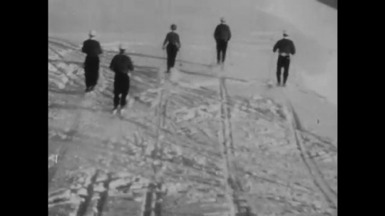 SWITZERLAND, 1950s: Tracking shot follows skiers down the mountain.