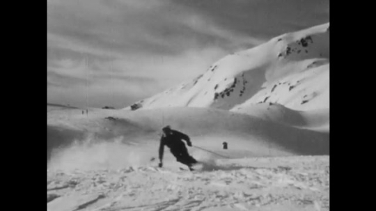 SWITZERLAND, 1950s: Medium shot of skiers going past camera followed by tilted frame.