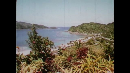 SAMOA AND TAHITI: 1960: View over mountains and bay. Pago Pago Intercontinental hotel from water. Tourists around swimming pool by sea. Lady dives into swimming pool.