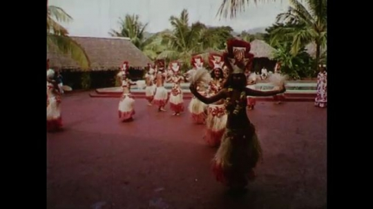 SAMOA AND TAHITI: 1960: Traditional dancers perform to hotel guests. Men make music with sticks and drums. Man dancing.
