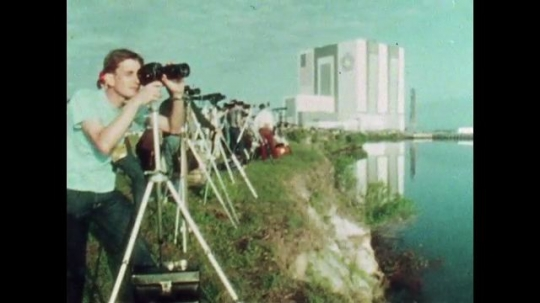 UNITED STATES: 1981: Man looking through camera. Cars parked on land next to water. People and cars waiting to watch space shuttle launch. River next to space shuttle launch site.