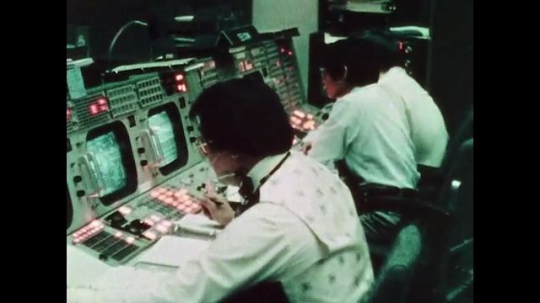 UNITED STATES: 1981: Man writing notes at ground control as he follows trajectory of space shuttle during launch. Man pointing at computer monitor during space shuttle launch.