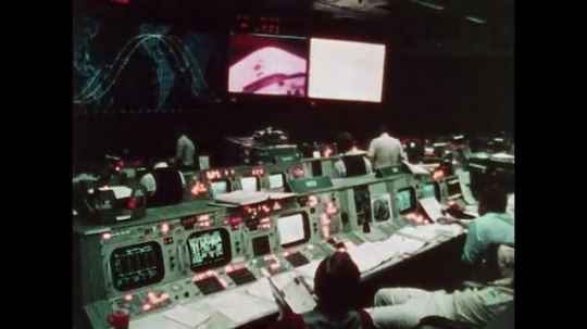 UNITED STATES: 1981: Close up view of space shuttle in space. People working at computers at space headquarters.
