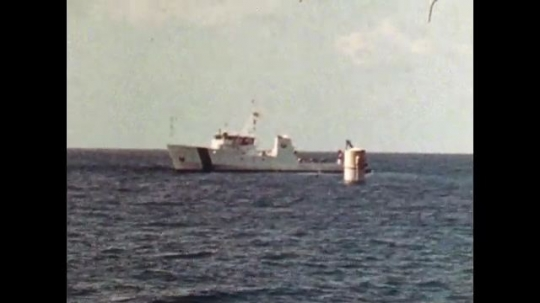 UNITED STATES: 1981: Boat floating on the ocean. Rocket being launched into sea. Cable being unraveled at sea. Man driving a boat.