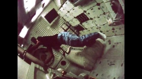 UNITED STATES: 1981: Astronaut floats through space shuttle cabin and up into hatch. Astronauts working inside cabin. View of Earth from space shuttle.