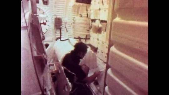 UNITED STATES: 1981: Astronaut safely stows items away inside shuttle. View of Earth from space shuttle. Two astronauts do somersaults inside space shuttle cabin.