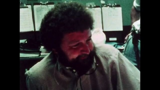UNITED STATES: 1981: NASA specialists laugh and smile as they relax at ground control. Men working at computers at NASA headquarters. Men look at photo of astronaut.
