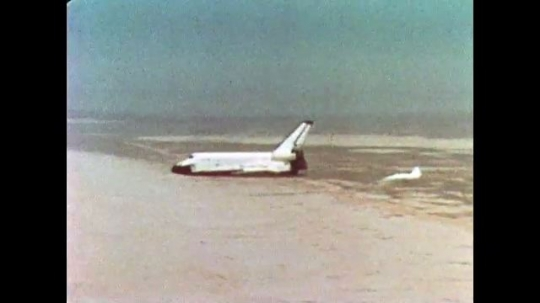 UNITED STATES: 1981: Space shuttle flies over desert escorted by jet planes. Shuttle lands on sand.