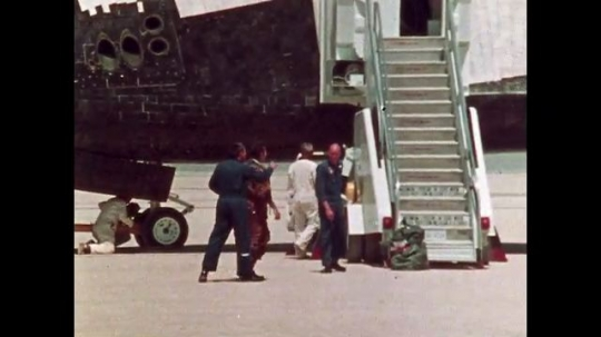 UNITED STATES: 1981: Astronaut walks around space shuttle after landing. Astronaut punches fist in air after landing. NASA headquarters team watch video after shuttle lands.