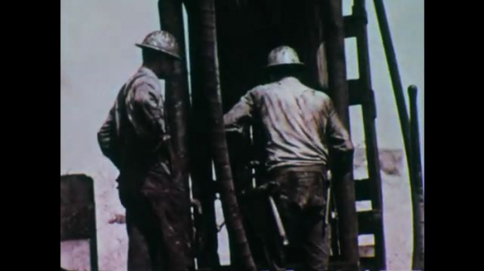 UNITED STATES: 1970s: Miners working above ground at mine shaft. Man drives crane. Man welding. Man hammers wood. Construction site