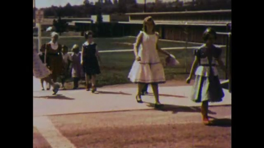 UNITED STATES 1960s: Two girls look both ways before crossing the street.