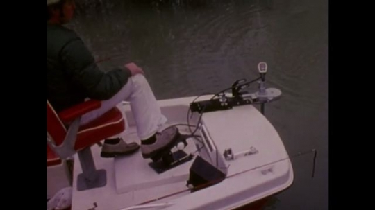 UNITED STATES: 1980s: foot controls boat pedal. Man catches fish on rod. Fish in water