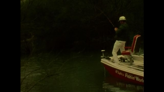 UNITED STATES: 1980s: man catches fish on rod. Men fishing from boat. Man picks up fish from water. Man shows fish to camera