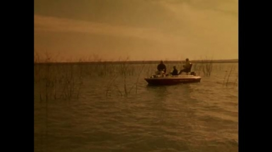 UNITED STATES: 1980s: boat travels past building in water. Man fishing