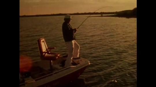UNITED STATES: 1980s: man on boat catches fish. Man holds fish. Man releases fish.
