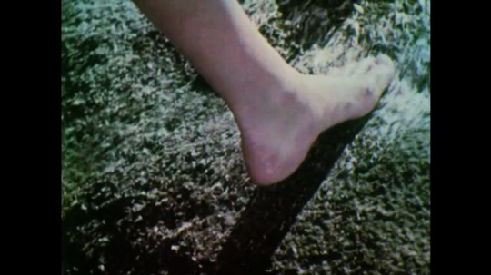 UNITED STATES, 1950s: Bare foot feeling a rock covered in wet seaweed. Bubbles on the surface of water.