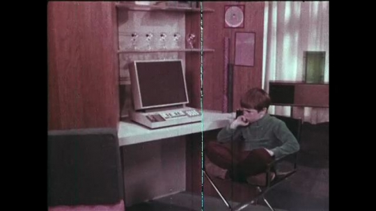 UNITED STATES: 1960s: Boy sits on computer chair and thinks. Boy switches computer on. Boy watches cartoons on computer screen.