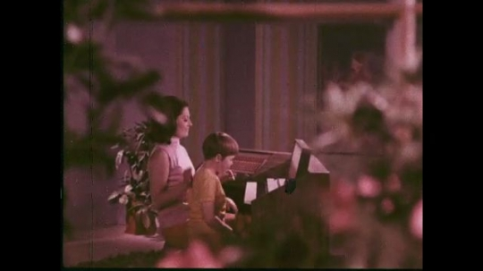 UNITED STATES: 1960s: Lady and boy practice on piano together. Lady turns buttons on electric piano and plays alongside boy.