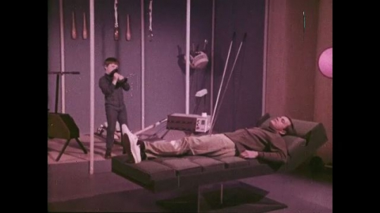 UNITED STATES: 1960s: Young boy lifts weights in home gym as man takes a nap on couch.