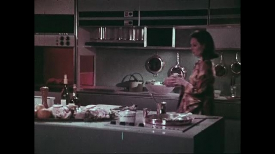 UNITED STATES: 1960s: Boy enters kitchen with lady. Lady prepares fruit in kitchen as she talks with boy.