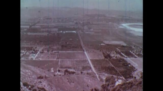 UNITED STATES: 1950s. Fields seen from above. Hand uses marker pen to draw transfer of heat energy from sun to fields on Earth. Heat bouncing off planet Earth into atmosphere.