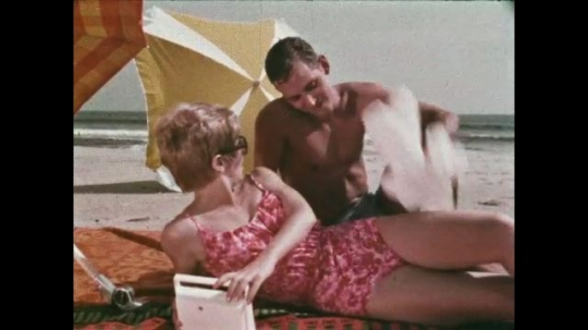 UNITED STATES: 1968: man and lady talk on beach. Wireless radio on side table. Lady writes letter at table. Close up of hands writing letter.
